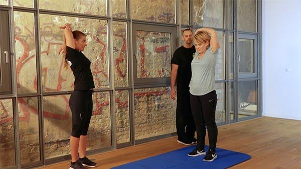 Andrea Ballschuh zusammen mit den X-DAYS Personal Trainern bei ihren Dehnungsübungen Abnehmen ohne Fitness-Studio